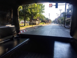 Sitting in the back of an empty songthaew